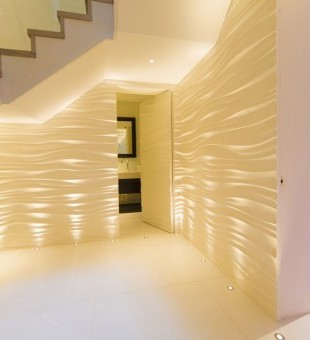 Combining soft up-lights with textured walls, transforms this plain space into a luxurious entertaining area.