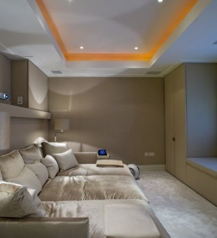 This snug basement cinema room is fully wired for internet connectivity and due to the nature of the thin and narrow room features a short-throw projector with a 2.35:1 fixed projector screen with 5.1 surround sound built into the ceiling