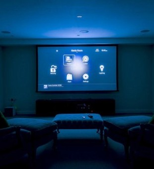 With the touch of a button on the Lutron keypad, the projector screen and projector will turn on, the lights will go down, and the Control4 interface will appear on the screen. Control the home technology in the media room via the Control4 remote.